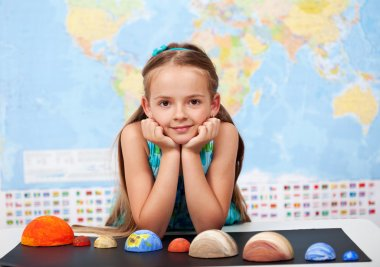 Little girl in elementary science class with her home project
