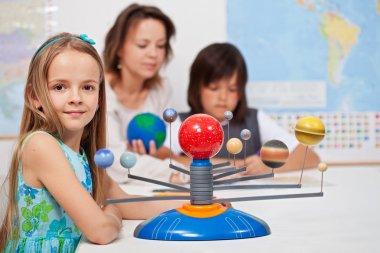 Kids study the solar system under their teacher supervision