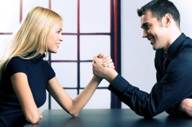 Young happy couple or business people fighting in arm-wrestling