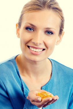 Smiling blond woman with Omega 3 fish oil capsules