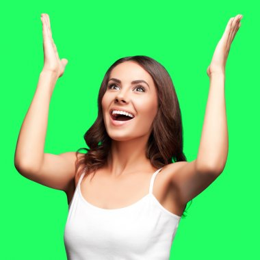 Happy gesturing woman looking up, on green chroma key background