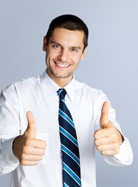 Businessman showing thumbs up gesture, on grey