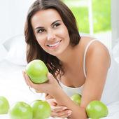 Happy usmívající se žena s zelenými jablky, uvnitř