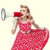 glückliche Frau mit Megafon in einem roten Kleid im Pin-up-Stil