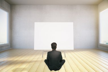 A man sits on the floor and looking at blank poster, mock up, 3d