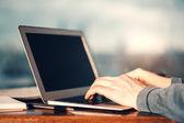 Mann mit grauen Ärmeln über Laptop-Tastatur eingeben