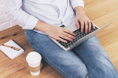 Man using laptop floor