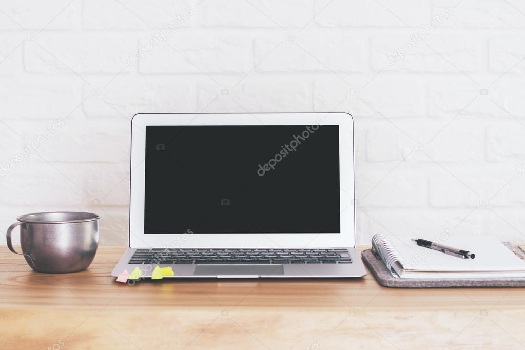 Vue de face de bureau en bois avec écran blanc ordinateur portable