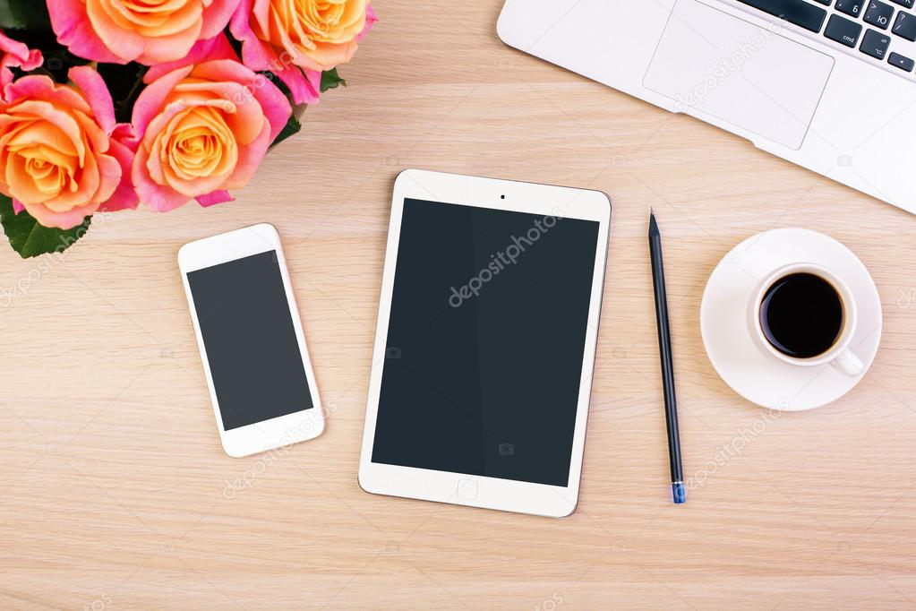 Top view of creative woman's desktop with roses, blank smart phone and tablet screens, coffee cup, pencil and laptop keyboard. Mock up
