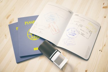 Passport with traveling stamps on light wooden desktop. Topview. Travel concept.