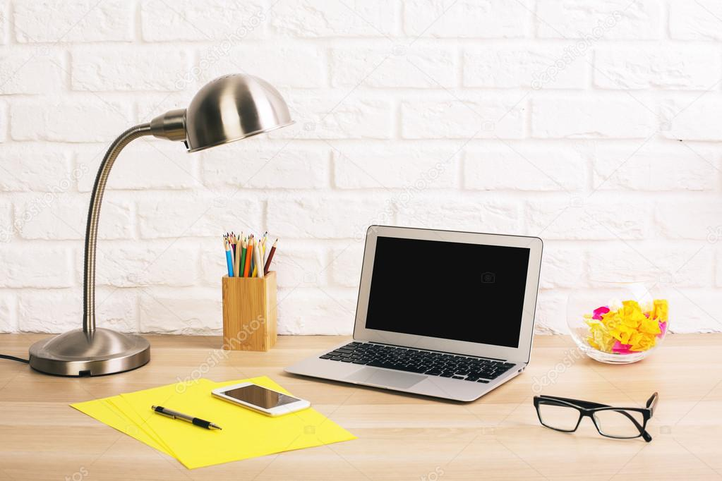 escritorio de diseo creativo con en blanco del ordenador porttil artculos de papelera lmpara