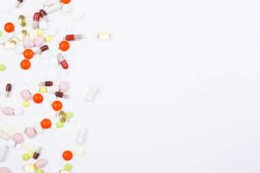 White surface with colorful pills and capsules on the left. Mock up stock vector
