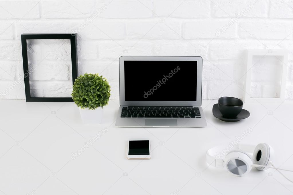 Front view of creative designer workplace with blank laptop screen ...