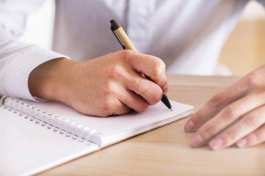 Man writing in notepad closeup