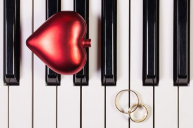 Piano keyboard,red heart and wedding rings