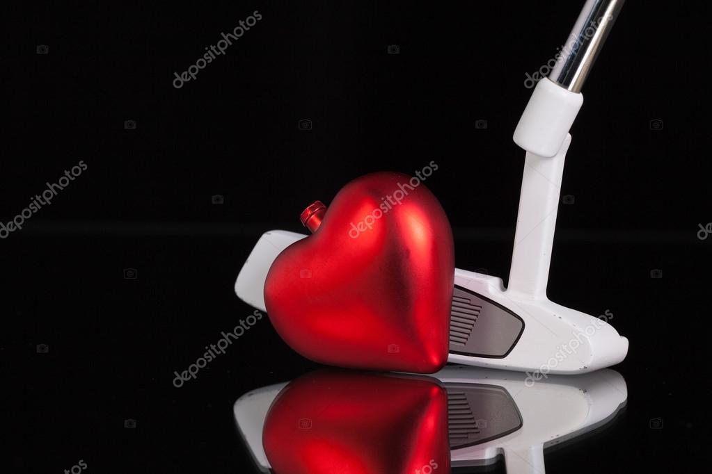 Putter de golf et le symbole de l amour sur le bureau en verre