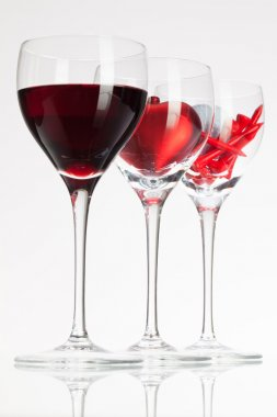 Wine glasses with red wine, heart and golf ball