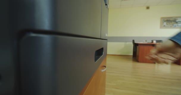 Aus nächster Nähe. Hände einer Frau, die im Büro Papier in einen Drucker legt.