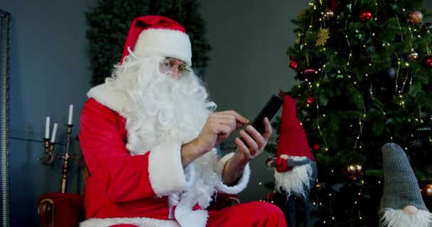Férfi Mikulás öltöny ül a nappaliban, és csevegés okostelefonnal video chat.