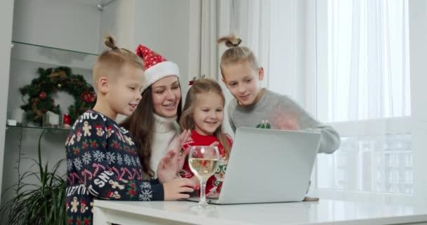 Szilveszter koncepció, anya és gyermekei karácsonyi jelmezben, hogy egy online hívás a laptop.