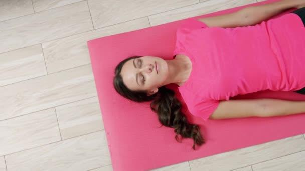Jóga doma. Mladá žena provádí jógu cvičení, relaxaci, ležící na podlaze