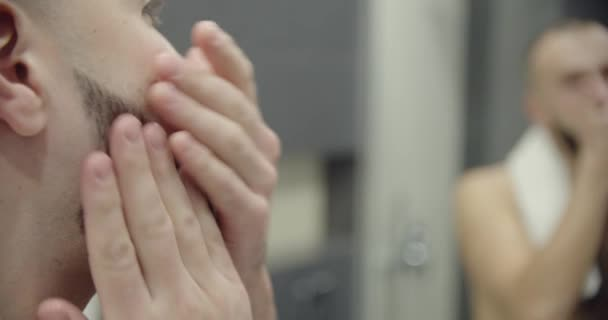 Nahaufnahme. Spiegelbild junger gutaussehender Mann berührt Bart, erschossen