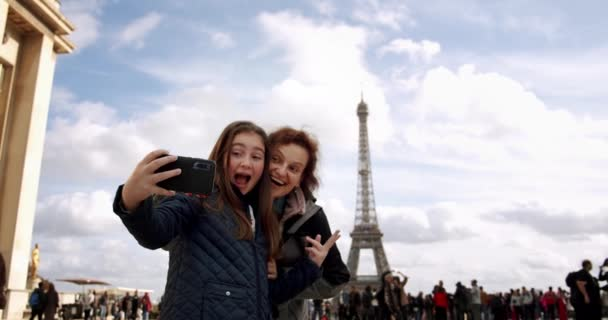 Happy loving mother and daughter taking a selfie photo on a smartphone and make funny faces cuddling together, on the background of Elfel on a sunny day France