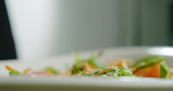Close up of sesame seeds fall into a salad. Slow motion