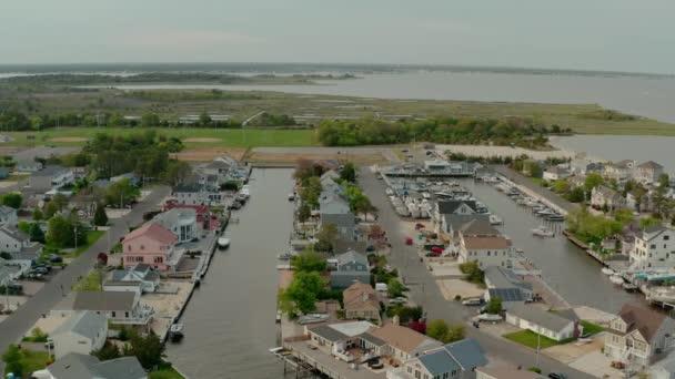 Drohnenaufnahme eines lokalen Wohnvororts am Fluss im Hinblick auf den weit entfernten Fluss Toms. Weitschuss der USA