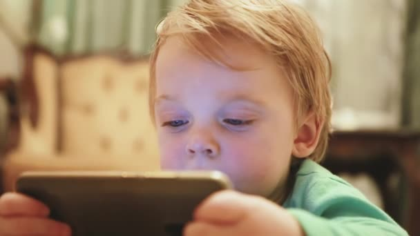 A charming European kid with a new smartphone watches interesting videos or cartoons while lying on the floor. Close-up of a little boy with a phone resting at home. Selective focus
