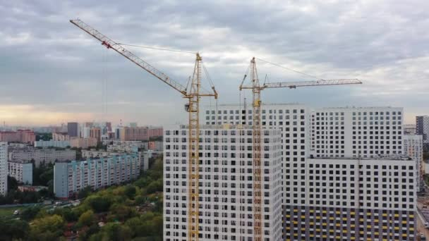 Building cranes and unfinished apartment houses under construction, drone tilt down shot