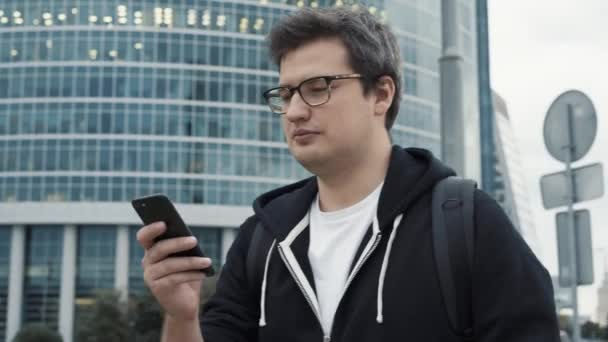 Mann läuft mit Handy vor Geschäftszentrum