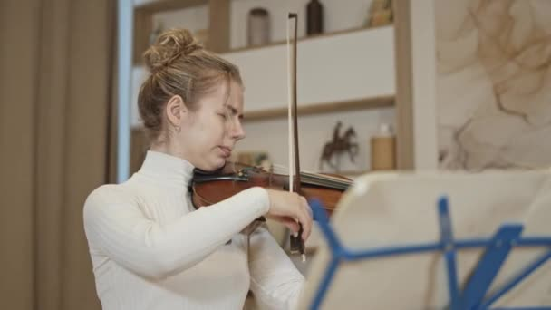 Mladá blondýna žena hraje na housle s hudbou stojí v luxusním interiéru domova