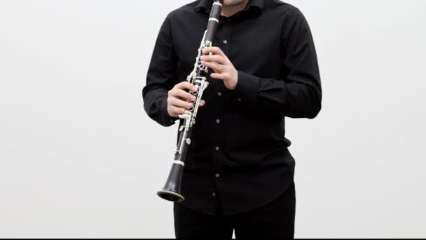Férfi fekete ruhában játszik klarinét álló fehér háttér