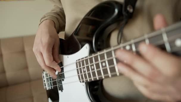 Hudebník s basovou kytarou v rukou doma