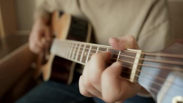 Hudebník hraje doma na lehkou akustickou kytaru