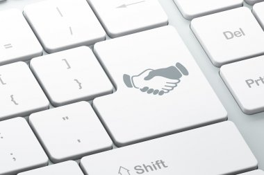 Business concept: Handshake on computer keyboard background