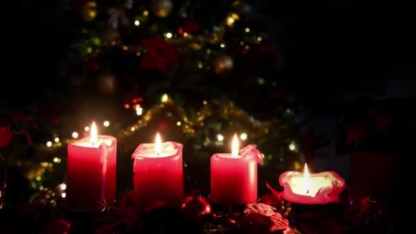 Weihnachten 4 Kerzen rot mit beleuchtetem Baum zum Hintergrund