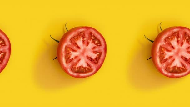 Mnoho čerstvě nakrájených červených rajčat animovaných na žlutém pozadí. Bezešvé smyčky potravin, minimální pohybový design umění se zeleninou.