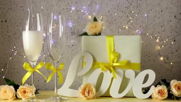 Šampaňské je nalito do sklenice. Dvě sklenice na šampaňské se žlutými luky stojící na stole s milostnými dopisy, dárkem a růžemi, bokeh světly, sv. Valentýna nebo svatební přání