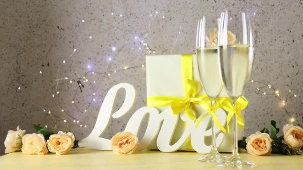 Dvě sklenice šampaňského se žlutými luky stojící na stole s milostnými písmeny, dárkem a růžemi, bokeh světly kruhů, selektivní zaostření, Svatý Valentýn nebo svatební přání