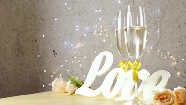 Dvě sklenice na šampaňské se žlutými luky stojící na stole s milostnými písmeny a růžemi válcovanými z kruhů, bokeh světly, sv. Valentýna nebo svatební přání
