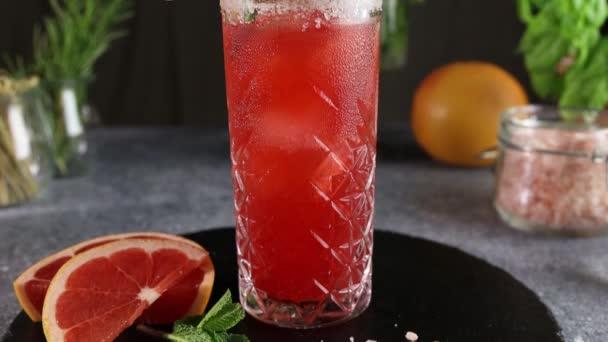 Rosa Grapefruit Mezcal Paloma Cocktail. Kamera bewegt sich entlang Highball Glas mit Wassertropfen. Nahaufnahme, geringe Schärfentiefe.