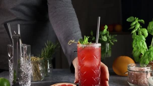 Frau legte auf das Tischglas rosa Grapefruit Mezcal Paloma Cocktail. Kamera bewegt sich entlang Highball Glas mit Wassertropfen. Nahaufnahme, geringe Schärfentiefe.