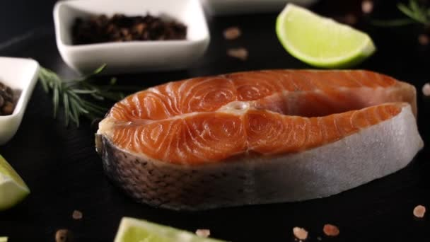 Nyers, friss lazac steak palatáblán és só, paprika, citrom, szegfűszeg és rozmaring. Lazacot és tengeri herkentyűt főzök. Egészséges étel koncepció. Lazac és fűszerek, körforgásban, közelről