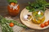Konzervované marinovaná rajčata v rajčatové šťávě na dřevěný stůl