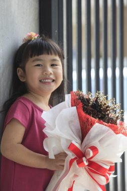 toothy smiling face of asian kid happiness emotion and dry flowe