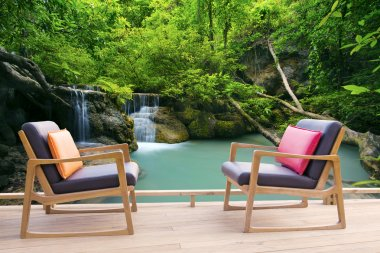 Relaxing wooden desk on wood terrace against beautiful waterfall
