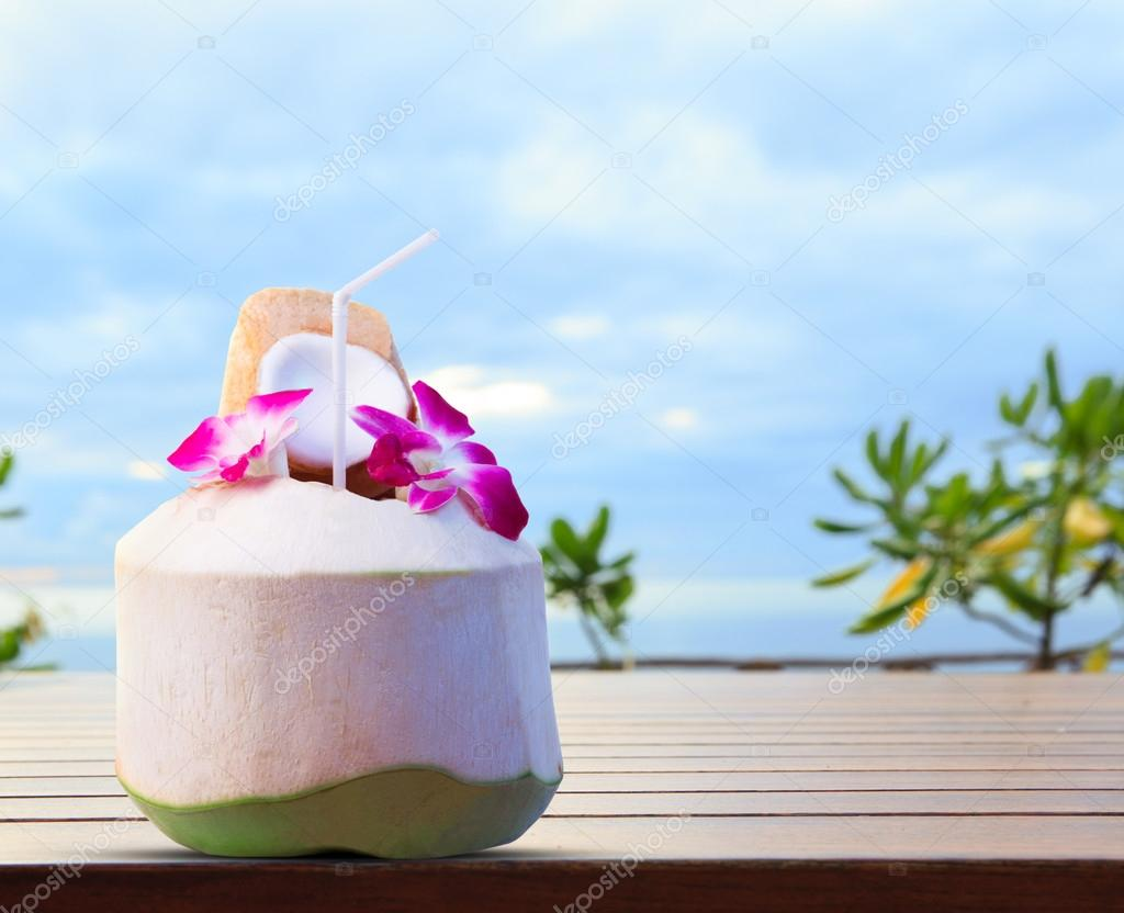 green coconut and orchid flowers as welcome drink in tropical de