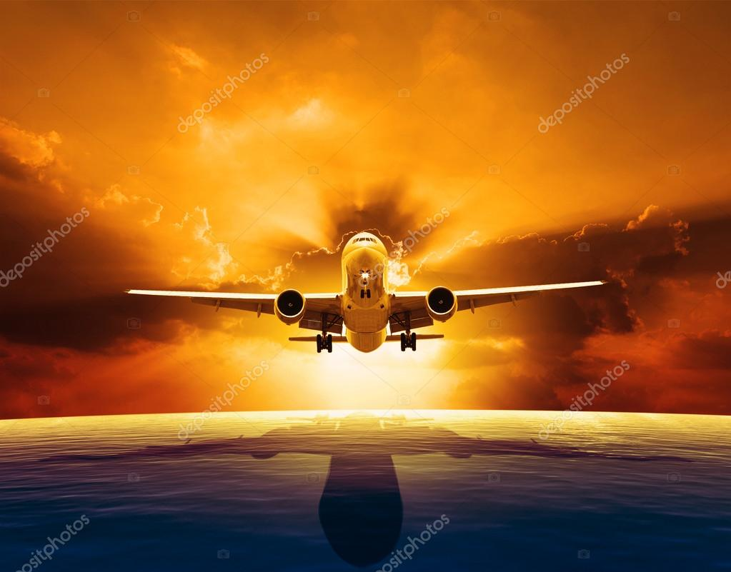 Passenger jet plane flying over beautiful sea level with sun set